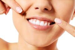Stomatologiczny zdrowia pojęcie - piękna kobieta wskazuje jej zęby zdjęcie royalty free