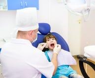 Stomatologicznym egzamininuje dawać mała dziewczynka dentystą Zdjęcie Stock