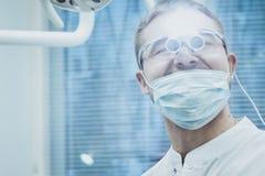 Stomatologie Zahnarztdoktor gl?nzt in den Augen eines speziellen Ger?tes lizenzfreie stockfotos