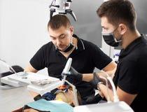 Stomatologist смотрит пациента около его ассистента в современной клинике стоковое фото rf