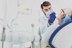 Stomatologist compétent soignant son patient Image libre de droits