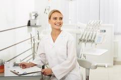Stomatologist contente bonito que senta-se no escritório dental fotos de stock royalty free