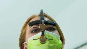 Stomatologist de la clínica que pone en la lupa dental de la venda, trabajando en belleza de los dientes metrajes
