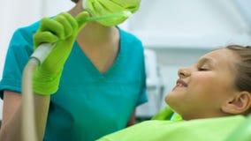 Stomatologist die speekseluitwerper, het geduldige kind glimlachen gebruiken, stelde klant tevreden stock footage