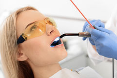 Stomatologist examining mouth of young woman Royalty Free Stock Image
