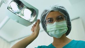 Stomatologist fêmea que ajusta luzes operatory dentais, controle, paciente POV filme