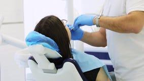 Stomatologist fait l'examen pr?ventif de la femme se reposant dans la chaise dentaire banque de vidéos