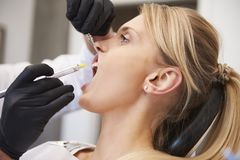 Stomatologist giving woman anesthesia in dentist`s clinic. Side view of stomatologist giving women anesthesia in dentist`s clinic royalty free stock photos