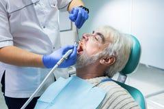 Stomatologist nettoie des dents Image libre de droits