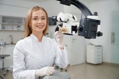 Stomatologist posing in dentistry near dental microscope. Happy female dentist posing in dentistry private clinic. Beautiful and charming blonde woman looking royalty free stock image
