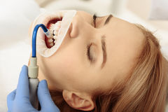 Stomatologist putting saliva aspirator in oral cavity of client Stock Images