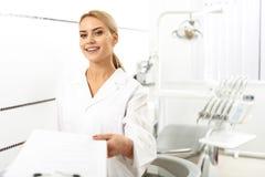 Stomatologist que da el espacio en blanco a su cliente en oficina Imagen de archivo