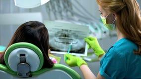 Stomatologist que muestra los dientes femeninos radiografía la imagen, cavidades, enfermedad periodontal foto de archivo