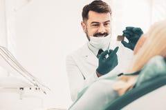 Stomatologist som visar röntgenfotografering till patienten arkivbild
