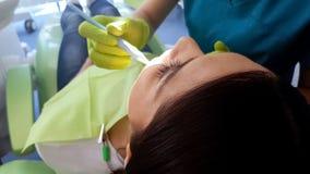 Stomatologo che tratta dente rotto femminile, rimozione della carie, disposizione del sigillante fotografia stock libera da diritti