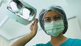 Stomatologo femminile che regola le luci operatory dentarie, controllo, paziente POV stock footage