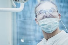 Stomatology. Dentist doctor shines in the eyes of a special device royalty free stock photos