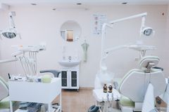 Stomatology interior of small dental clinic with professional chair in green colors. Dentistry, medicine, medical equipment and. Stomatology concept. White tone royalty free stock photos