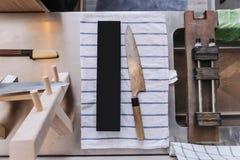 Stomp en rustiek Japans keukenmes wachtend op het scherpen op blauwe strook witte stof met het scherpen van materiaal af stock foto's
