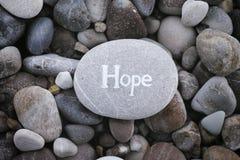 Stone με την ελπίδα λέξης στο υπόβαθρο πετρών στοκ εικόνα
