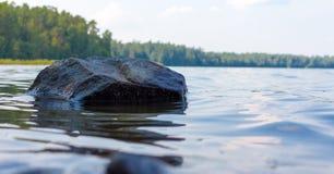 Stone που προεξέχει από το ήρεμο νερό στη λίμνη Στοκ Εικόνες