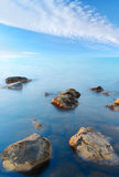 Stone. Two stones on foregrounds in calm sea water Stock Image
