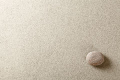 Stone. Beige stone at right side of sand background Stock Images