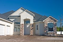 Stone accents new home. Newly constructed home with stone accents on columns and partial face Stock Image