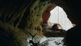 Stone age man in cave. Neanderthal man goes to warm up at bonfire in his cave. Snowy winter outside