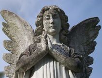 Stone Angel. A very old weathered stone angel still watches over Stock Photo