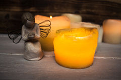 Stone angel and candle light. On wooden background Stock Photos