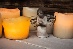 Stone angel and candle light. On wooden background Stock Image