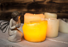 Stone angel and candle light. On wooden background Royalty Free Stock Image