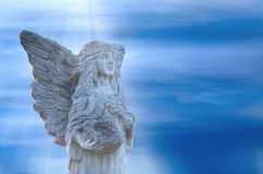 Stone angel statue in light beams. Stone angel statue standing within soft light beams from Heaven with a stormy background. The angel is holding a flower rimmed Royalty Free Stock Photos