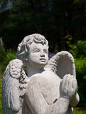 Stone angel statue praying and looking skyward Stock Photo