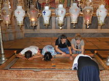 STONE OF ANOINTING, CHURCH OF THE HOLY SEPULCHRE, JERUSALEM, ISRAEL. Jerusalem, Israel – October 12, 2015: Believers praying on the Stone of Anointing, the Stock Photos