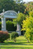 Stone arbor with large pillars and decorative stucco against the background of the green park zone... For your design Royalty Free Stock Image