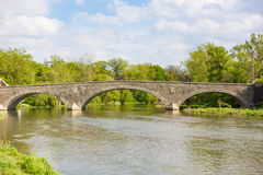 Stone arc bridge over humber river. Solid stone bridge with three arcs over humber river in a natural environment with trees and a cloudy blue sky Royalty Free Stock Photo