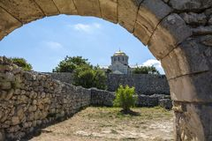 Ancient Arch and St. Vladimir Cathedral in the background. Stone arch in the ancient city of Hersonissos royalty free stock image