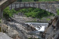 Stone arch bridge Bellows falls, Vermont. River under stone arch bridge outside power plant in Bellows Falls, Vermont stock photo