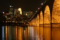 Stone Arch Bridge, Minneapolis. The Stone Arch Bridge at night. Downtown Minneapolis is in the background, and the Mississippi River in the foreground Stock Photography