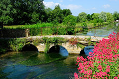 Stone arch bridge over the canal in beautiful cottage in Cotswolds, England, UK. Stone arch bridge over the canal beside with flowers in beautiful cottage in Royalty Free Stock Image