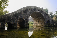 Stone arch bridge over river at sunny winter noon. Stone arch bridge over the river at sunny winter noon,Huanglongxi town,Chengdu,China Royalty Free Stock Photo