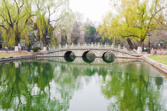 Stone arch bridge reflection in pond royalty free stock photography