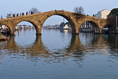 Stone arch bridge reflection in pond Royalty Free Stock Image