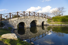 Stone arch bridge reflection view on a lake in a park with blue sky background. At the beginning of spring season Royalty Free Stock Photos