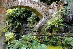 A stone arch decorates the garden Stock Photography