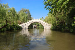 Stone arch footbridge in an Asian garden Royalty Free Stock Image