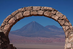 Stone arch in front of a volcano in chile. Arch made of stone in front of a volcano in chile Royalty Free Stock Images