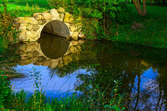 Stone Arch among Green Grass over Lake Stock Photography
